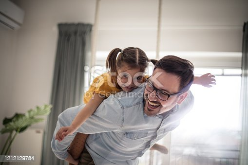 Free as can be. Father and daughter having fun at home.