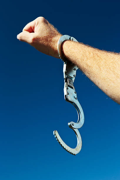 Free at last! Hand with clenched fist and open handcuff stock photo