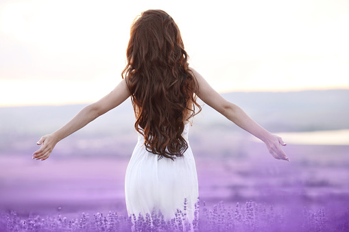 Free brunette woman with open arms enjoing sunset in lavender