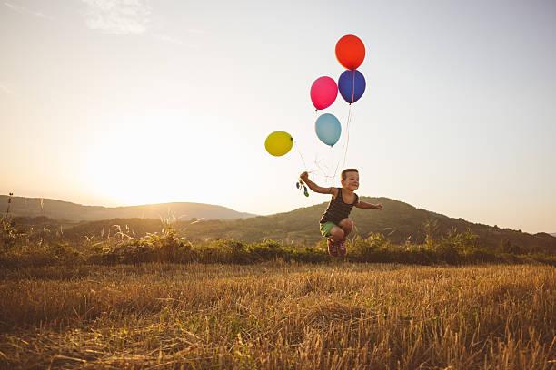 free child playing with balloons - ballonhose stock-fotos und bilder