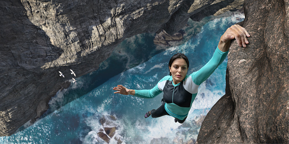 A young woman extreme free climbing without safety equipment, hangs one handed from a rock face over the sea and rocks below. The climber is wearing climbing top, leggings. chalk bag and climbing shoes. Waves break over rocks in the sea below during sunny daylight in clear weather.