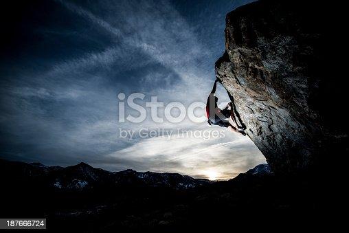 A man free climbing a steep boulder