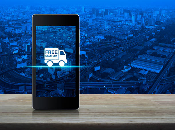 free delivery truck icon on smart phone screen on table - iphone gratis stock-fotos und bilder