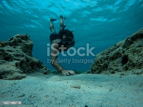Free diver reaching for sea shells at the bottom of the sea