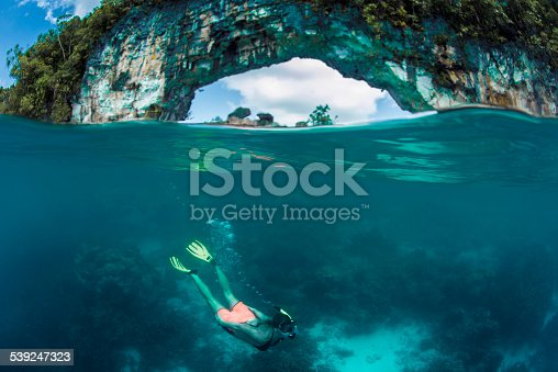 Female diver in Palau, with  the iconic Rock island Arch in the background