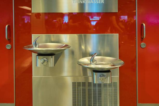 kostenloses trinkwasser am changi airport, singapore - indoor wasserbrunnen stock-fotos und bilder