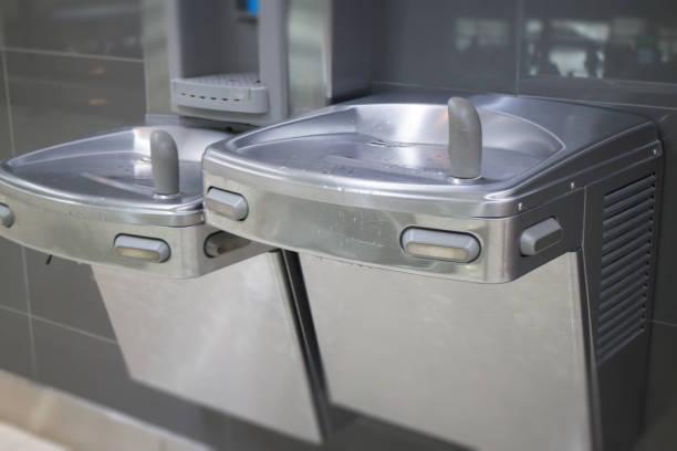 kostenloses trinkwasser für reisende am flughafen - indoor wasserbrunnen stock-fotos und bilder