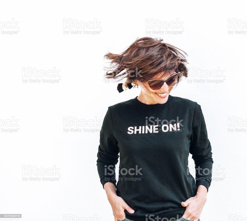 Kostenlose Gefühl glücklich lächelnde Frau posiert in schwarzem Sweatshirt mit positiven Druck Shine On – Foto