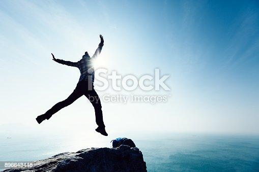 istock free female hiker jumping on sunrise seaside cliff edge 896643448