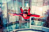 Flight in the Indoor Skydiving. The man is flying in the wind tunnel. Free flight in the Simulator of Free-fall. Aerodynamic tunnel. The wind tunnel is a device used for free floating.
