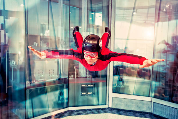 Free flight in the wind tunnel. Flight in the Indoor Skydiving. The man is flying in the wind tunnel. Free flight in the Simulator of Free-fall. Aerodynamic tunnel. The wind tunnel is a device used for free floating. aerodynamic stock pictures, royalty-free photos & images