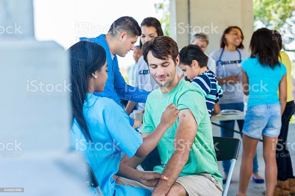 Free flu shot clinic with a handsome man recieving vaccination stock photo