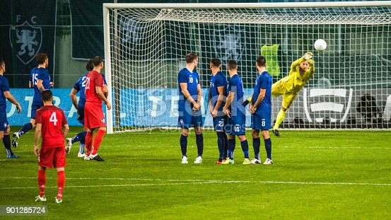 Soccer goalkeeper in yellow preparing to defend the goal from the ball that is flying over the human defensive wall.