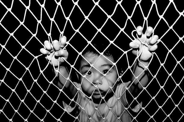 free me a child looking for help to free her from imprisonment behind the net concept image. trafficking stock pictures, royalty-free photos & images