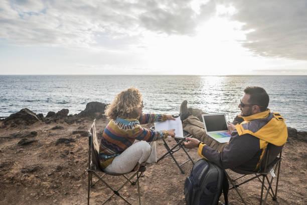 kostenlose moderne alternative paar reisender mann und frau mittleren alters sitzen vor den ozean mit internet-computer-laptop arbeiten und studieren mit papier-buch - leute auf der bewegung genießen weltweit-konzept - neue abenteuer stock-fotos und bilder
