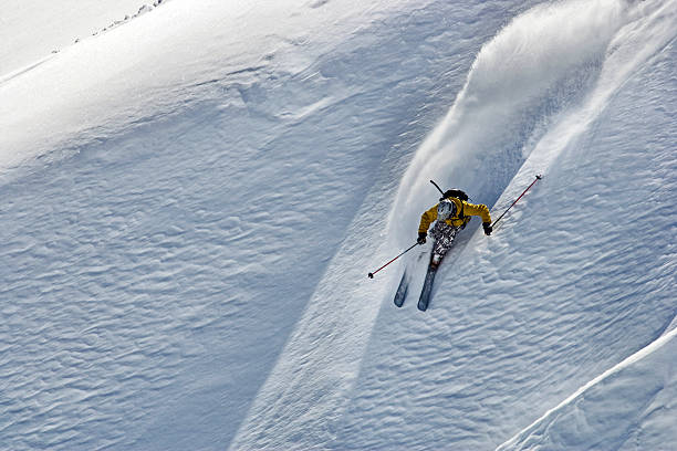 free ride skier turning in powder snow free ride skier making high speed left turn in fresh powder snow steep stock pictures, royalty-free photos & images