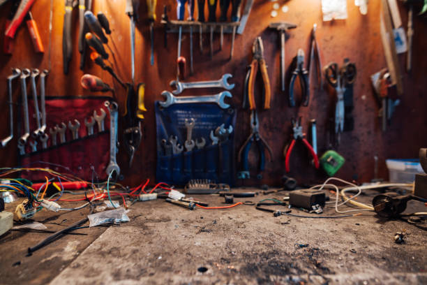 Free space on a dirty table in   workshop, on the background of a hanging instrument Free space on a dirty table in the workshop, on the background of a hanging instrument workbench stock pictures, royalty-free photos & images
