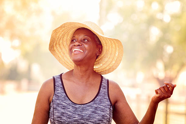 Free spirited senior African American woman Free spirited senior African American woman smiling in a Summer hat, snapping her fingers to the rhythm of a happy life. snapping stock pictures, royalty-free photos & images