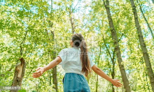 istock Free woman breathing clean air in nature forest. Happy girl from the back with open arms in happiness. Fresh outdoor woods, wellness healthy lifestyle concept. 1269532812