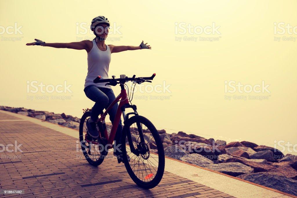 free woman cyclist riding bike on sunrise seaside – zdjęcie