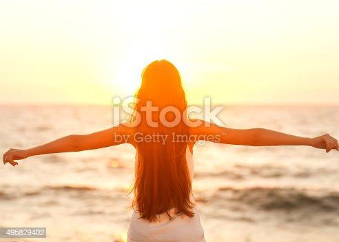 istock Free woman enjoying freedom feeling happy at beach at sunset. 495829402