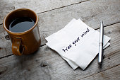 Coffee cup written with napkin that free your mind reminder on the wooden table