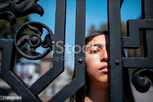 Headshot of the young women looking through the fence