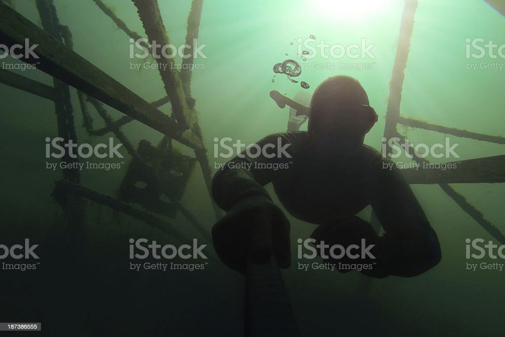 Freediver going deep in the water with structure above him stock photo