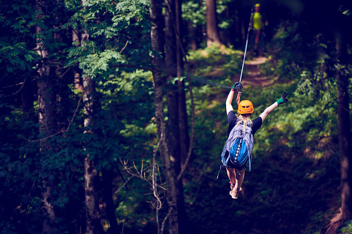 rear view of young woman in the forest enjoying the adventure on the zip line, having fun and holding her arm raised.