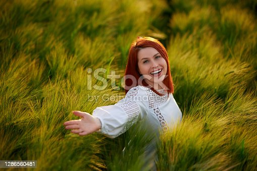 Redhead looking at camera with toothy smile feeling happy with arms outstretched in the wheat field