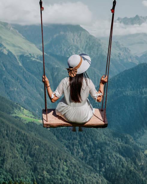 freedom and carefree of a young female on a swing - balouço imagens e fotografias de stock
