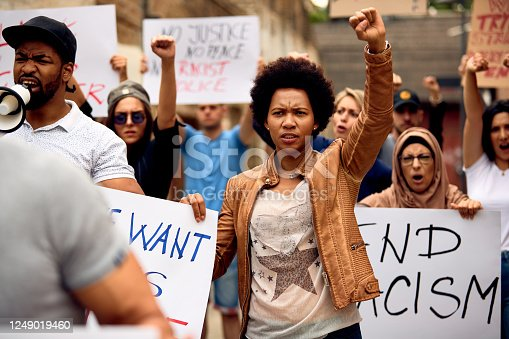 Multi-ethnic crowd of people protesting against racism on city streets. Focus is on African American woman with raised fist.