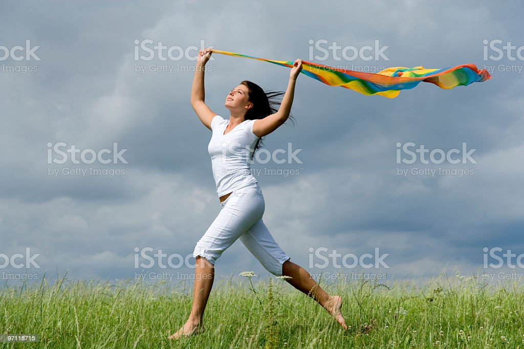 Freedom and fun - Happy young woman running over meadow royalty-free stock photo