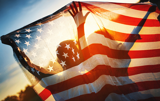 Closeup rear view of a couple holding American flag against summer sunset. They are visible as silhouettes.