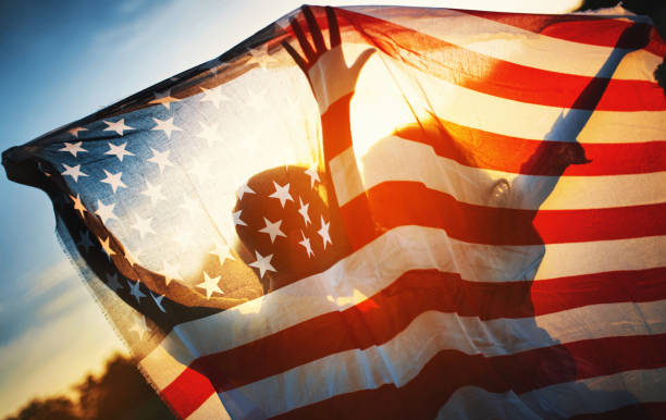 Freedom and Love in the USA Closeup rear view of a couple holding American flag against summer sunset. They are visible as silhouettes. american culture stock pictures, royalty-free photos & images