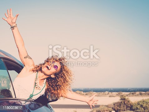 Freedom and travel happy laughing people concept with beautiful caucasian young woman out of the car enjoying the destination place opening arms and shouting free - ocean in background and sun