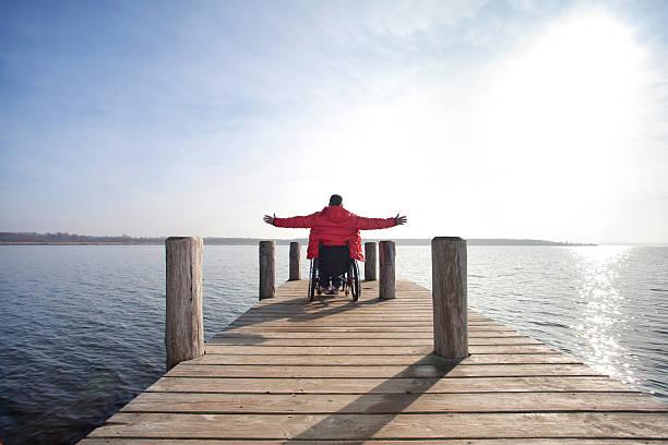 freedom at lake man in wheelchair enjoying his freedom at lake paraplegic stock pictures, royalty-free photos & images
