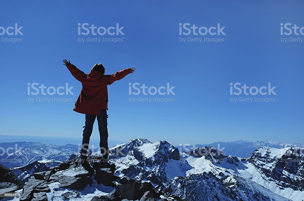 Freedom being depicted by a person standing on a mountain royalty-free stock photo