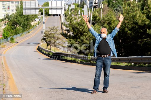 Freedom, Curfew at Ankara with empty streets with on Active Senior Man under Coronavirus period with unrecognizable pedestrian.