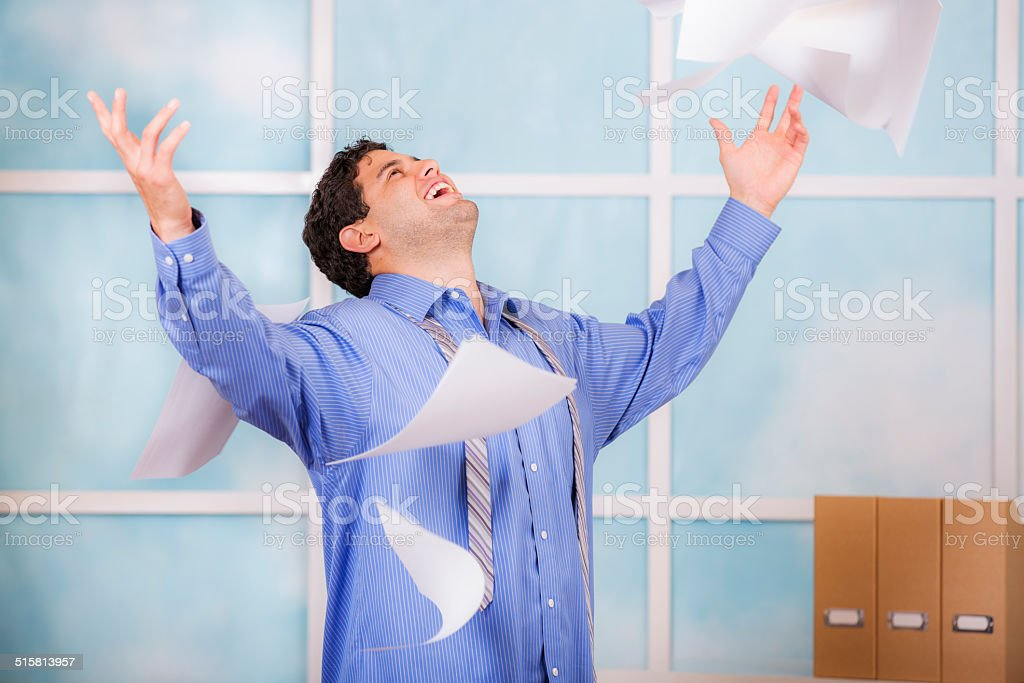 Freedom! Excited business man throws papers in air. Office. stock photo