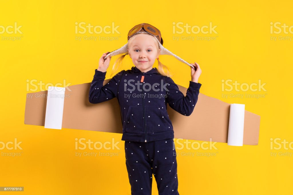 Freedom, girl playing to be airplane pilot, funny little girl with aviator cap and glasses, carries wings made of brown cardboard as an airplane stock photo