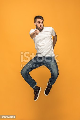 Freedom in moving. Mid-air shot of handsome happy young man jumping and gesturing against orange studio background. Runnin guy in motion or movement. Human emotions and facial expressions concept