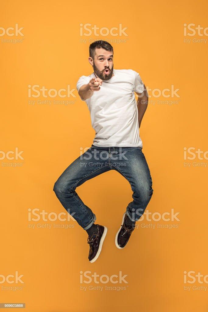Freiheit in der Bewegung. hübscher junger Mann orange Hintergrund springen – Foto