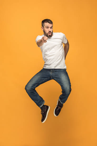 freedom in moving. handsome young man jumping against orange background - mid air stock pictures, royalty-free photos & images