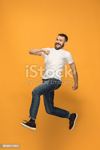 664626542 istock photo Freedom in moving. handsome young man jumping against orange background 959924052