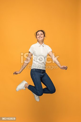 664626542 istock photo Freedom in moving. Pretty young woman jumping against orange background 962463828