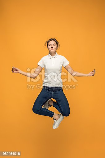 664626542 istock photo Freedom in moving. Pretty young woman jumping against orange background 962464018