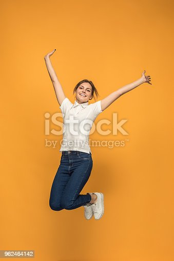 664626542 istock photo Freedom in moving. Pretty young woman jumping against orange background 962464142