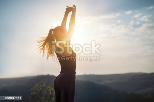 Young women in sports clothing feeling freedom in nature, doing gymnastics on sunset  with lens flare.