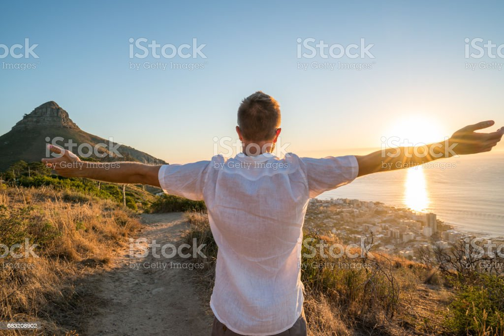 Freedom in nature, man arms outstretched at sunset foto de stock royalty-free